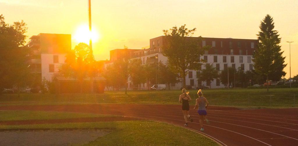 Sonnenuntergang mit zwei Läuferinnen auf Leichtathletikbahn